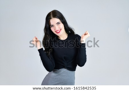 Concept of business female photo portrait with emotions. Portrait of a brunette girl with a smile with long hair with excellent makeup in a gray dress on a white background in different poses.