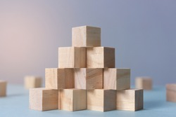 Concept of business growth to success. Stack of wooden cube as pyramid stairs with selective focus and depth of field.