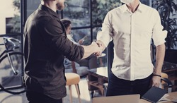 Concept of business partnership handshake.Closeup photo two businessmans handshaking process.Successful deal after great meeting in coworking studio.Horizontal, blurred background