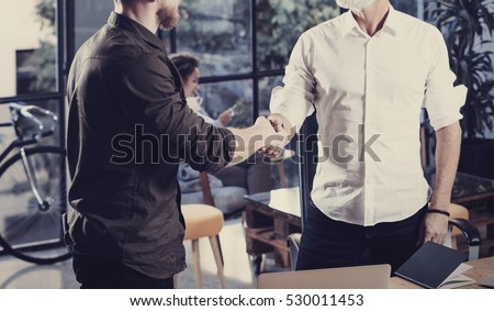 Concept of business partnership handshake.Closeup photo two businessmans handshaking process.Successful deal after great meeting in coworking studio.Horizontal, blurred background #530011453