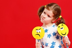 concept of children's emotions. child girl chooses between a sad and joyful smile on  colored red background