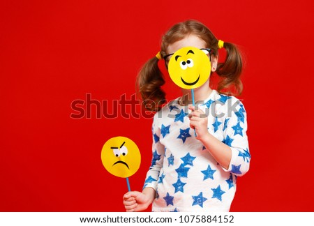 concept of children's emotions. child girl chooses between a sad and joyful smile on  colored red background #1075884152
