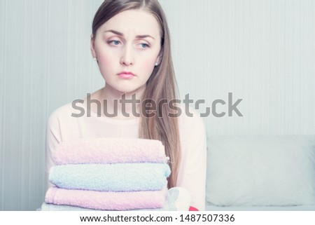 Concept of chores. Sad housewife with a stack of clean linen in her house, copy space, toned #1487507336
