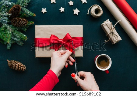 Concept of Christmas items on a table. Woman\'s hands wrapping Christmas gift
