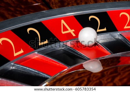 Concept of classic casino code 2-2-4-2-2 lucky numbers roulette wheel with black and red sectors and white ball #605783354