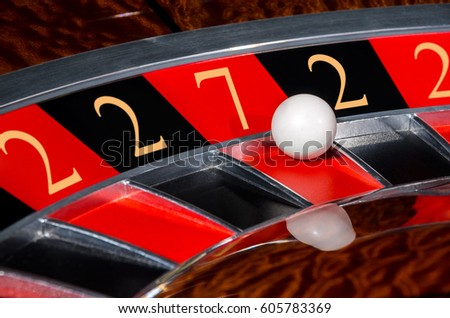 Concept of classic casino code 2-2-7-2-2 lucky numbers roulette wheel with black and red sectors and white ball #605783369