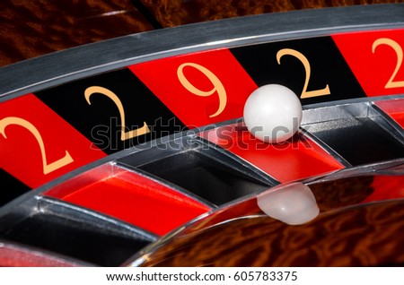 Concept of classic casino code 2-2-9-2-2 lucky numbers roulette wheel with black and red sectors and white ball #605783375