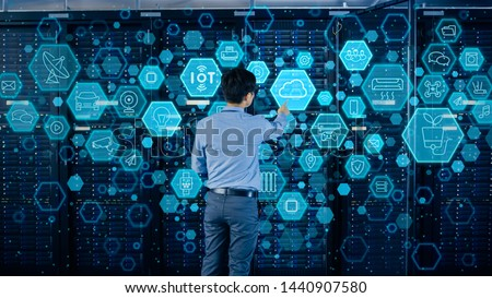 Concept of Cloud Data Storage. Shot In the Modern Data Center: IT Engineer Standing Beside Open Server Rack Cabinet and Touching Digital Illustrative Icons with Different Symbols and Visualisations. #1440907580