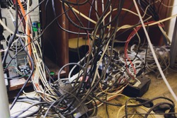Concept of clutter in office. Unwound and tangled electrical wires under the table.