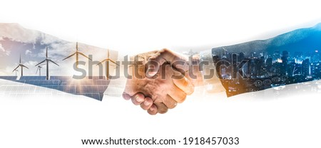 Concept of collaboration to change the world to reduce global warming,energy sources for renewable,sustainability by alternative energy.Double exposure of handshake of wind turbine and night city.
