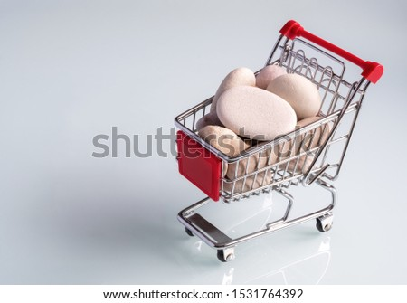 Concept of consumerism: Small shopping cart loaded with a pile of stones on a gray background
