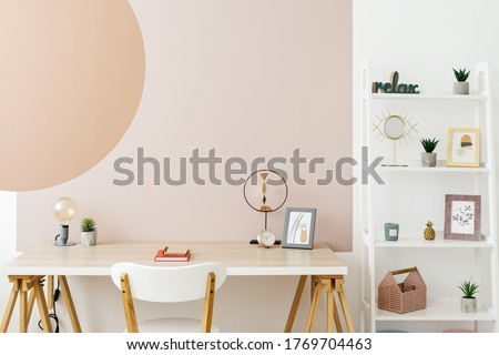 Concept of contemporary workplace. Modern room with minimal interior, decor at wooden table, shelves, chair and graphic painting on copy space wall Сток-фото ©