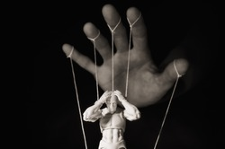 Concept of control. Marionette in human hand. Black and white image