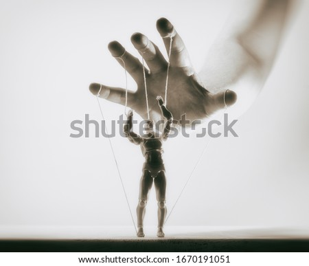 Concept of control. Marionette in human hand. Black and white image. Foto stock ©