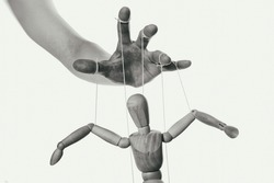 Concept of control. Marionette in human hand. Close-up. Black and white.