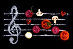 Concept of cooking pizza, like notes from ingredients. Salami, tomato and mozzarella cheese on a black background with a treble clef.