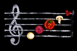 Concept of cooking pizza, like notes from ingredients. Salami, tomato and mozzarella cheese on a black background with a treble clef