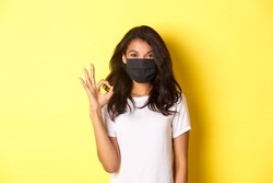 Concept of coronavirus, pandemic and lifestyle. Portrait of smiling african-american woman in face mask, showing okay sign in approval, recommend or guarantee something, yellow background