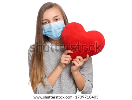 Concept of coronavirus quarantine. COVID-19 - home self isolation. Child wearing medical protective face mask to health protection from influenza virus, isolated on white. Teen girl holds red heart.
