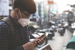 Concept of coronavirus quarantine. MERS-Cov, Novel coronavirus (2019-nCoV), man with medical face mask using the phone to search for news.Air pollution