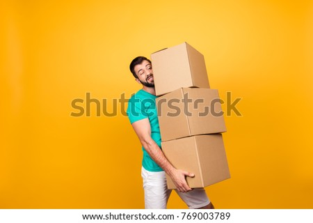 Concept of courier and messenger service. Grimacing handsome guy is trying to keep big stack of cardboard bosex in his hand, isolated on yellow background