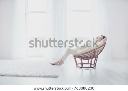 Concept of coziness, serenity and relaxation. Life is good! Pretty beautiful calm joyful woman in casual outfit is sitting on the modern armchair in her roomy flat and having a daytime nap