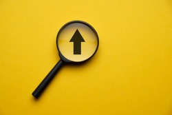 Concept of creativity and growth of business development - magnifier with a black arrow on a yellow background. Close up.