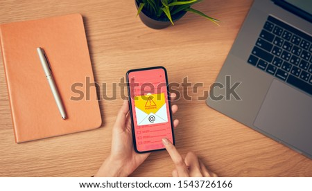 Concept of cyber crime, hand holding smartphone and show malware screen that comes with email, hack password from bank accounts and personal data.