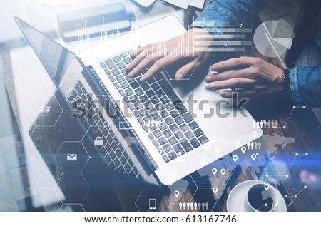 Concept of cyber security.Man working at sunny office on laptop while sitting at the wooden table.Background of digital screen,virtual worldwide connection icon,diagram,graph interfaces.Blurred