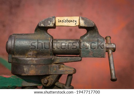Concept of dealing with problem. Vice grip tool squeezing a plank with the word insistency Stock photo ©
