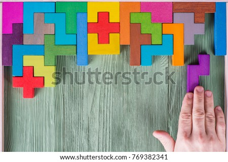 Concept of decision making process, logical thinking. Find the missing piece of the proposed. Hand holding puzzle element. Background with colorful shapes wooden blocks #769382341