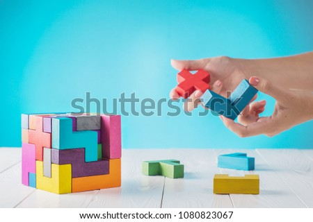 Concept of decision making process, logical thinking. Logical tasks. Conundrum, find the missing piece of the proposed. Hand holding wooden puzzle element. Hand sets the last element of the puzzle.  #1080823067