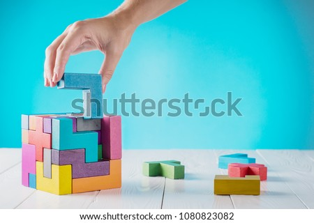 Concept of decision making process, logical thinking. Logical tasks. Conundrum, find the missing piece of the proposed. Hand holding wooden puzzle element. Hand sets the last element of the puzzle.