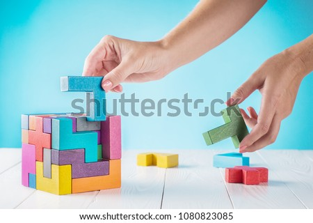 Concept of decision making process, logical thinking. Logical tasks. Conundrum, find the missing piece of the proposed. Hand holding wooden puzzle element. Hand sets the last element of the puzzle.  #1080823085