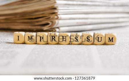 Concept of dices with letters forming word: Impressum (German for Imprint). Generic newspaper background with some blurred text on the bottom and paper stack in the back.