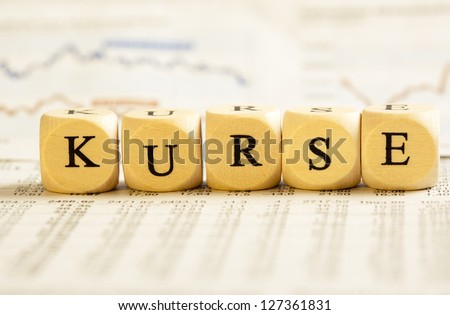 Concept of dices with letters forming word: Kurse - German for stock values. On generic newspaper background with stock market numbers and some blurred charts.