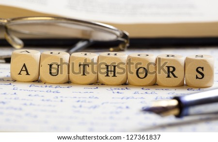 Concept of dices with letters forming words: Authors. Generic handwritten text, pen, glasses and books as background.  Dices made from wood with natural imperfections.