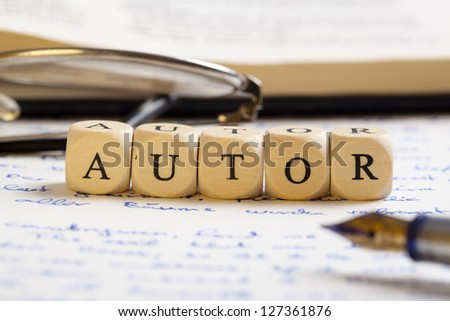 "Concept of dices with letters forming words: Autor (German version of ""author""). Generic handwritten text, pen, glasses and books as background.  Dices made from wood with natural imperfections"