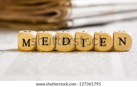 Concept of dices with letters forming words: Medien (German for Media). Generic newspaper background with some blurred text on the bottom and paper stack in the back.