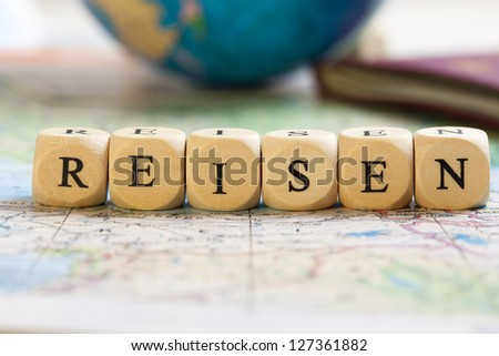 Concept of dices with letters forming words: Reisen (German for travel). Blurred map, globe and passport as background.  Dices made from wood with natural imperfections.