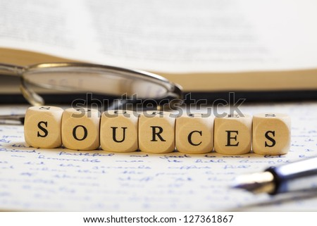 Concept of dices with letters forming words: Sources. Generic handwritten text, pen, glasses and books as background. Dices made from wood with natural imperfections.