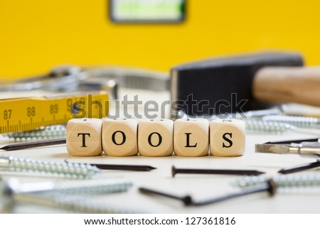 Concept of dices with letters forming words: Tools. Surroundings and background of hammer, screws, nails and other tools. Dices made from wood with natural imperfections.