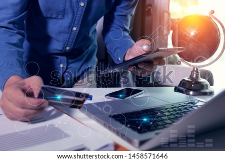 Concept of digital diagram,graph interfaces,virtual screen,connections icon, Young businessman using smartphone with holding a credit card and laptop computer at modern office and morning sun light. #1458571646