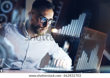 Concept of digital diagram,graph interfaces,virtual screen,connections icon.Young entrepreneur working at modern office on laptop.Man using digital touch pad at night,blurred background.Horizontal
