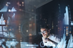 Concept of digital diagram,graph interfaces,virtual screen,connections icon.Young finance analist working at modern office.Man using contemporary laptop at night,blurred background.Horizontal