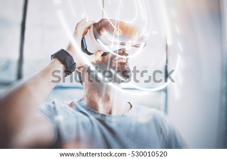 Concept of digital screen,connection and interfaces.Attractive bearded man enjoyingvirtual reality glasses in modern loft studio.Smartphone using with VR goggles headset.Flare effect,blurred #530010520