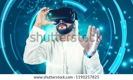 Concept of digital screen,connection and interfaces.Beraded Arab man enjoying virtual reality glasses in modern design.  VR goggles headset. #1190257825