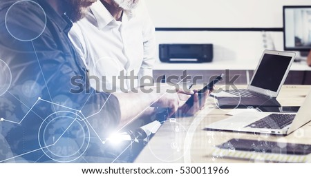 Concept of digital screen,virtual connection icon,diagram,graph interfaces.Bearded young man holding mobile phone and touching display.Adult businessman working together with partner.Film effect,wide. #530011966