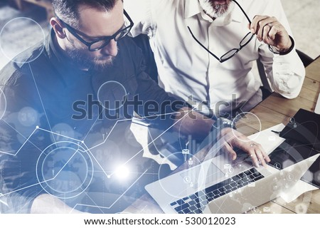 Concept of digital screen,virtual connection icon,diagram, graph interfaces.Closeup view of bearded man working together with adult businessman colleague at the wooden table.Flare,blurred #530012023