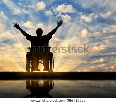 Concept of disability and disease. Silhouette happy disabled person in a wheelchair at sunset and reflection in water